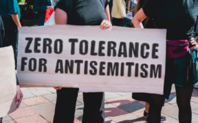 """The phrase """" Zero tolerance for antisemitism """" drawn on a carton banner during a protest against rising antisemitism. (AndriiKoval/Shutterstock)"""