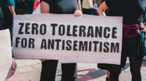 "The phrase "" Zero tolerance for antisemitism "" drawn on a carton banner during a protest against rising antisemitism. (AndriiKoval/Shutterstock)"